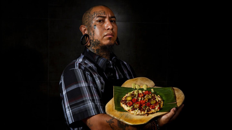 Chef Eddie Garcia displays tlayuda de chorizo y chapulines (tlayudas with crispy chorizo and toasted grasshoppers) at Cocina Condesa in Los Angeles.
