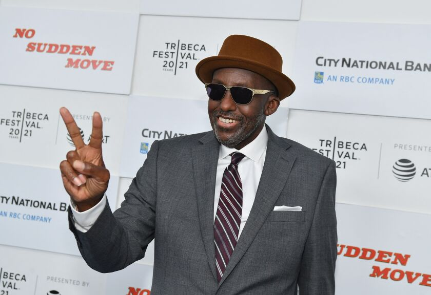 A man wearing sunglasses and a hat makes a peace sign while walking the red carpet at a film festival.