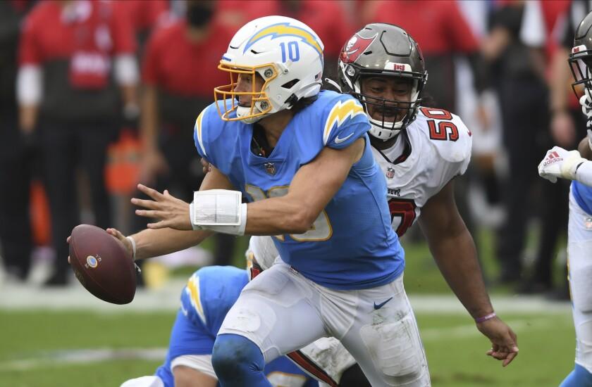 Chargers quarterback Justin Herbert scrambles away from Tampa Bay Buccaneers nose tackle Vita Vea.