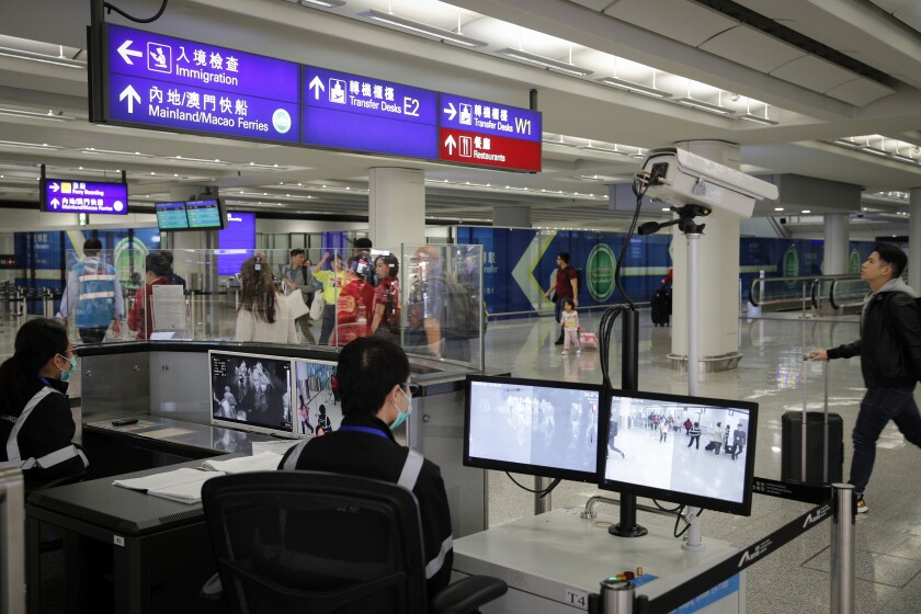 FILE - In this Jan. 4, 2020, file photo, health surveillance officer use temperature scanner to monitor passengers arriving at the Hong Kong International airport in Hong Kong. The possibility that a new virus in central China could spread between humans cannot be ruled out, though the risk of transmission at the moment appears to be low, Chinese officials said Wednesday, Jan. 15, 2020. (AP Photo/Andy Wong, File)