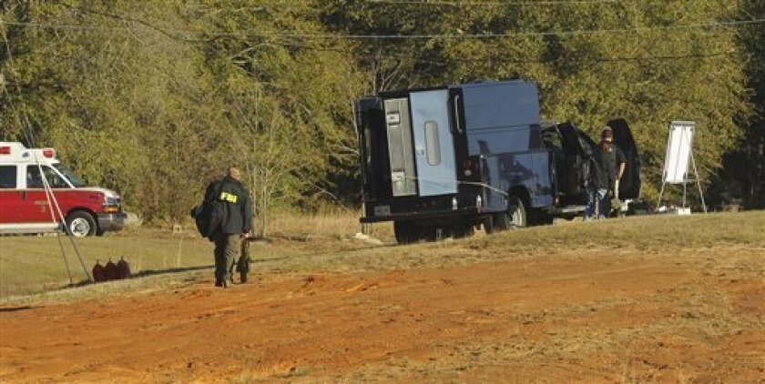 Police and emergency personnel remain on site at the property of Jimmy Lee Sykes, a suspect accused of holding a 5-year-old boy hostage in an underground bunker on Saturday Feb.  2, 2013 in Midland City, Ala. Negotiators were still trying to persuade Jimmy Lee Dykes to surrender. Police have said t