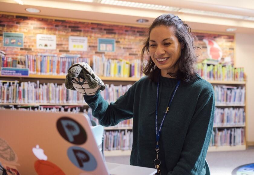Una mujer presenta un espectáculo de marionetas virtual en una sucursal de la Biblioteca Pública de Los Ángeles.