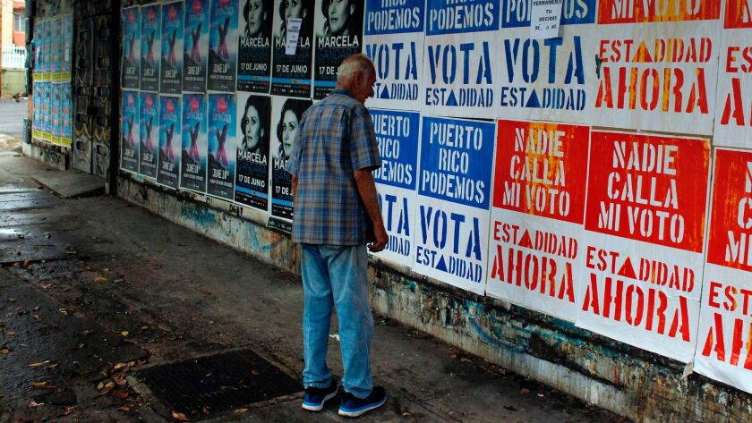 A man reads campaign posters promoting statehood for Puerto Rico in San Juan.