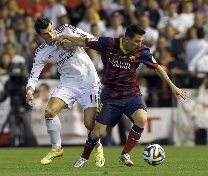 El delantero argentino del FC Barcelona Leo Messi (d) trata de escapar del galés Gareth Bale, del Real Madrid, durante un partido. EFE/Archivo