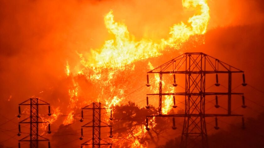 Flames burn near power lines in Montecito, Calif., in December. (Mike Eliason / Associated Press)