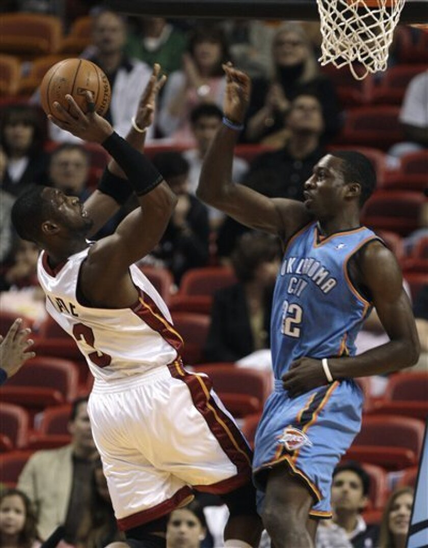Miami Heat guard Dwyane Wade (3) shoots as Oklahoma City Thunder forward Jeff Green, right, defends in the first quarter during an NBA basketball game in Miami, Saturday, Dec. 6, 2008. (AP Photo/Lynne Sladky)