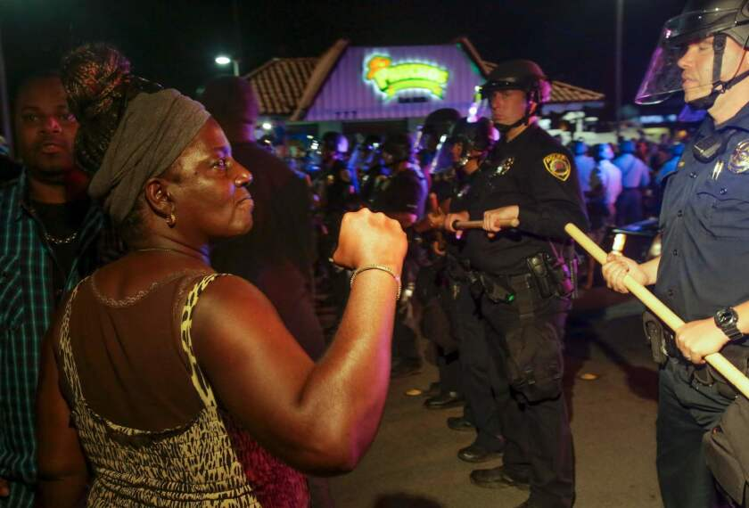 Protesters march following the fatal police shooting of an unarmed black man said to be mentally ill. Local officials urged calm and pledged a full investigation.