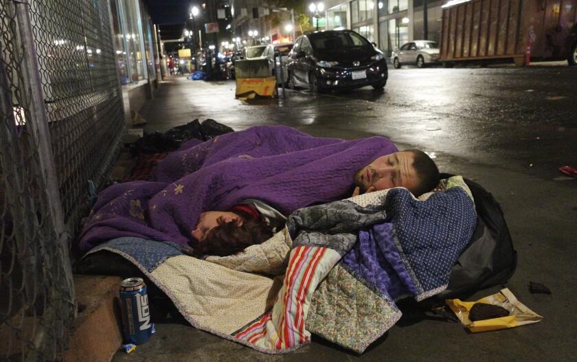 Two people sleep on a street in downtown Portland