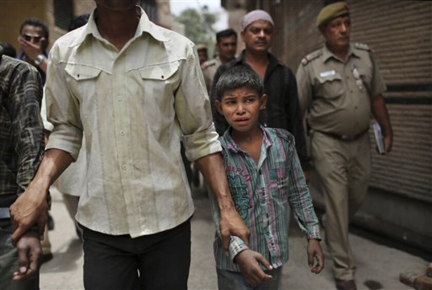 A young Indian bonded child laborer cries as he is walked away after being rescued during a raid by workers from Bachpan Bachao Andolan, or Save the Childhood Movement, at a garment factory in New Delhi, India, Tuesday, June 12, 2012. Raids on factories in the Indian capital revealed dozens of migr