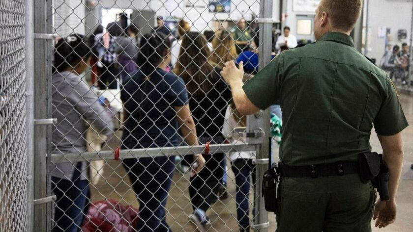 In this photo provided by U.S. Customs and Border Protection, a U.S. Border Patrol agent watches as people who've been taken into custody related to cases of illegal entry into the United States stand in line at a facility in McAllen, Texas, on June 17, 2018.