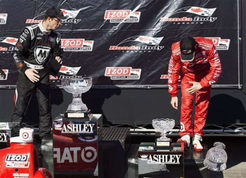 Winner Scott Dixon, right, attempts to save second-place finisher Sebastien Bourdais' trophy after it slipped off the stand as it was handed to him, at the IndyCar auto race Saturday, July 13, 2013, in Toronto. (AP Photo/The Canadian Press, Michelle Siu)