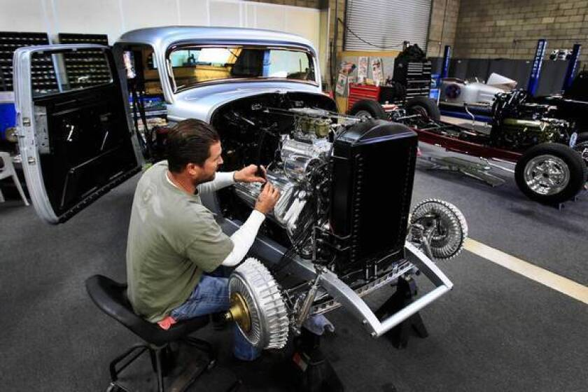 Jimmy Shine, manager at So-Cal Speed Shop in Pomona, works on a 1932 Ford owned by Bill Lindig of Houston, which Shine was preparing for display at the Grand National Roadster Show at the Fairplex.