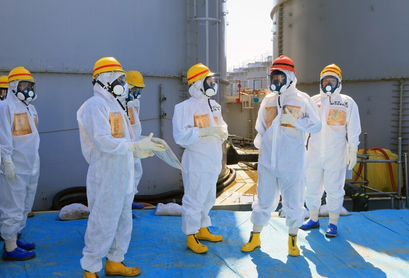 Japanese Prime Minister Shinzo Abe, in orange hard hat, is briefed during a tour of the stricken Fukushima Daiichi nuclear power complex.