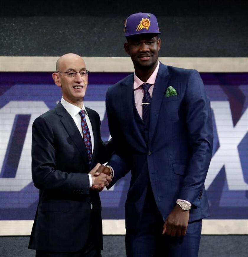 El comisionado de la NBA, Adam Silver (i) se da la mano con Deandre Ayton, elegido número uno por Phoenix Suns en la primera ronda del draft de la NBA 2018, en el Barclays Center en Brooklyn, Nueva York (EE.UU.) hoy, jueves 21 de junio de 2018. EFE