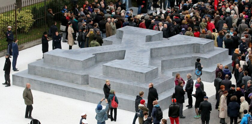 People surround a memorial dedicated to deserters of the Nazi Wehrmacht troops and victims of their military justice during its unveiling ceremony in downtown Vienna, Austria, Friday, Oct. 24, 2014. The memorial is located in front of the presidential office in the Hofburg palace and the federal ch