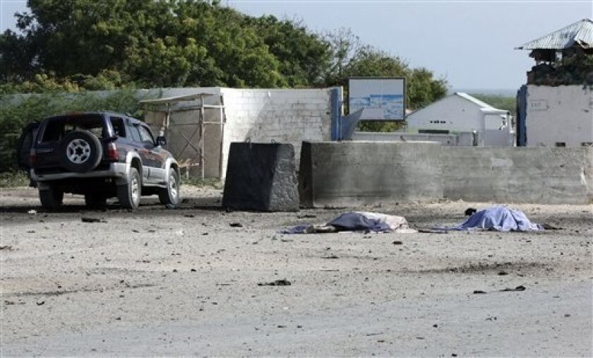 Two bodies lie in front of the Mogadishu airport gate Thursday, Sept. 9, 2010. A suicide car bomber and gunmen attacked the front gate to Mogadishu's seaside airport on Thursday, triggering an explosion and gunbattle, officials said. Several people were killed, including security forces. The coordinated attack was the latest in a surge of assaults by Islamist insurgents, who last month declared a new, stepped-up effort to oust the country's weak government. The barrage took place about 40 minutes after Somalia's president flew out of the country. After the car bomb exploded, a second vehicle full of militants opened fire at African Union and Somali security forces, said Osman Dahir, a police officer at the airport. He said there were several dead bodies of insurgents lying in front of the airport, but he didn't know how many.(AP Photo/Farah Abdi Warsameh)