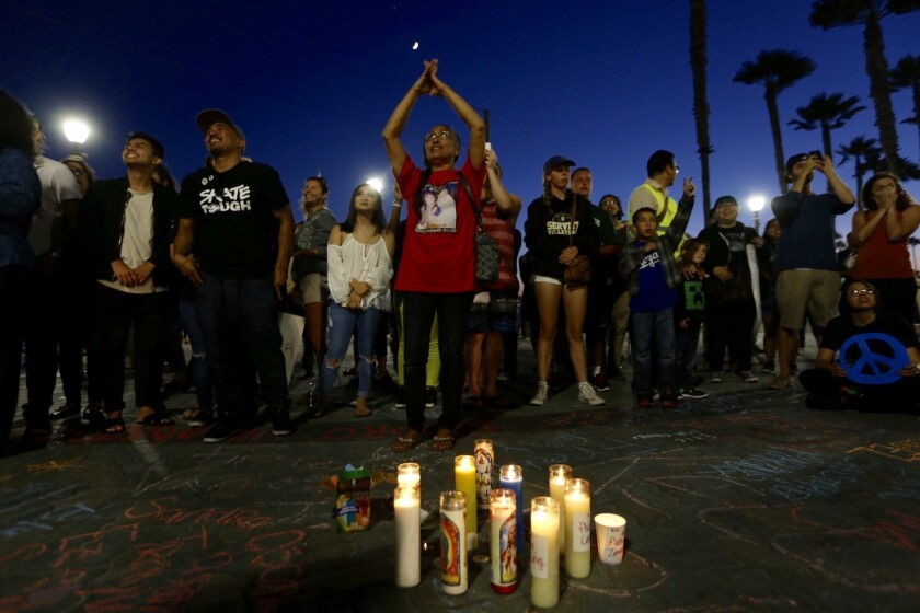 Theresa Smith, center, of Placentia, joins about two dozen people at a vigil at the Huntington Beach Pier for victims of violence.