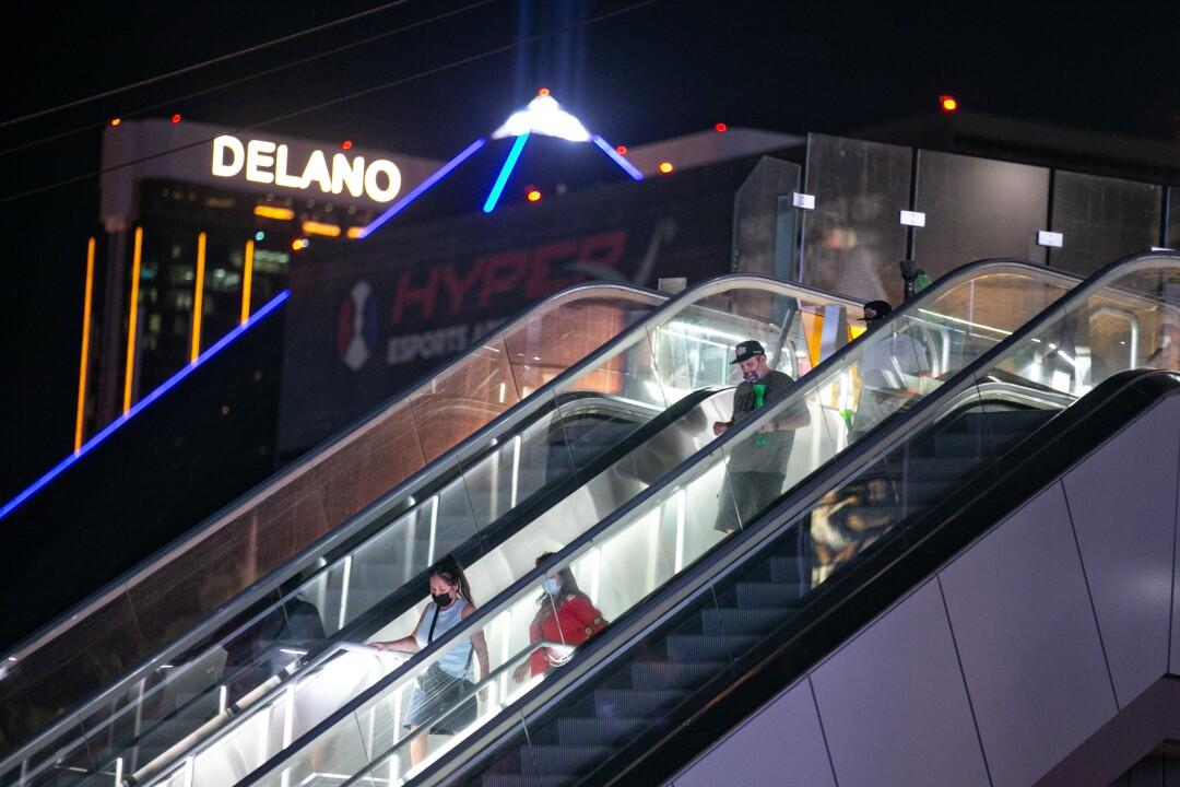 چندین مرد نقابدار در پله برقی در نوار لاس وگاس سوار می شوند