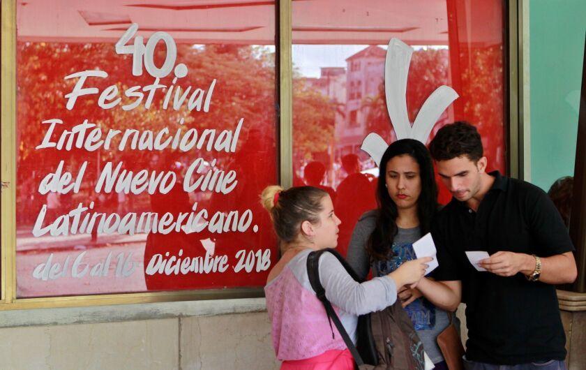 Varios jóvenes conversan al lado de un cartel que anuncia la 40 edición del Festival del Nuevo Cine Latinoamericano que se realiza ya en La Habana (Cuba).