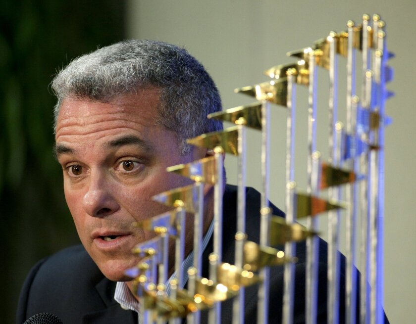 FILE - IN this Nov. 5, 2015, file photo, Kansas City Royals general manager Dayton Moore speaks to members of the media along side the Royals' World Series trophy during a news conference wrapping up the team's season, in Kansas City, Mo. The Royals have signed general manager Dayton Moore and mana
