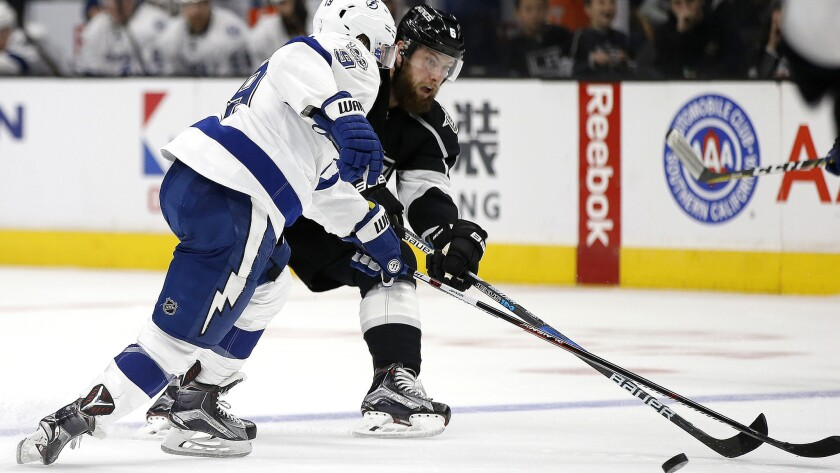 Kings defenseman Jake Muzzin, right, sends the puck up ice while under pressure from Lightning center Tyler Johnson during the second period Monday.