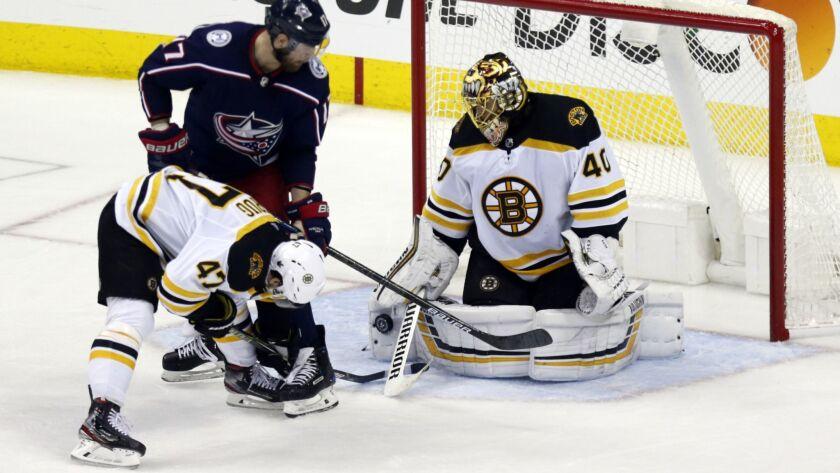 Boston Bruins goalie Tuukka Rask, right, of Finland, stops a shot by Columbus Blue Jackets forward B