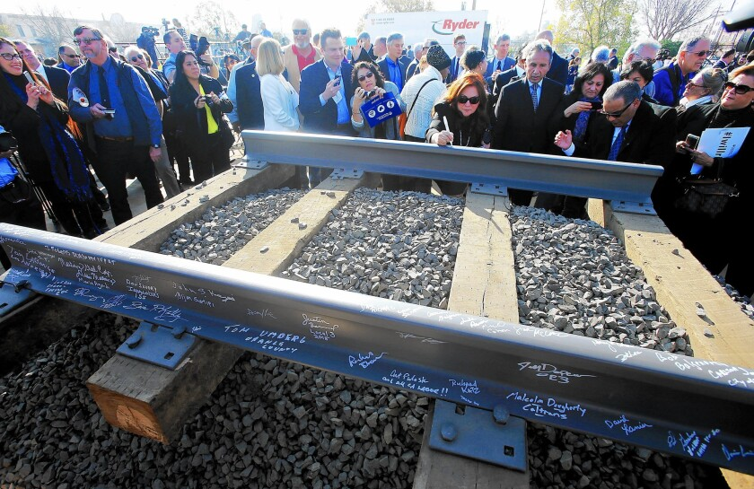 Guests sign segments of railroad track during a January groundbreaking ceremony for a bullet train station in Fresno.