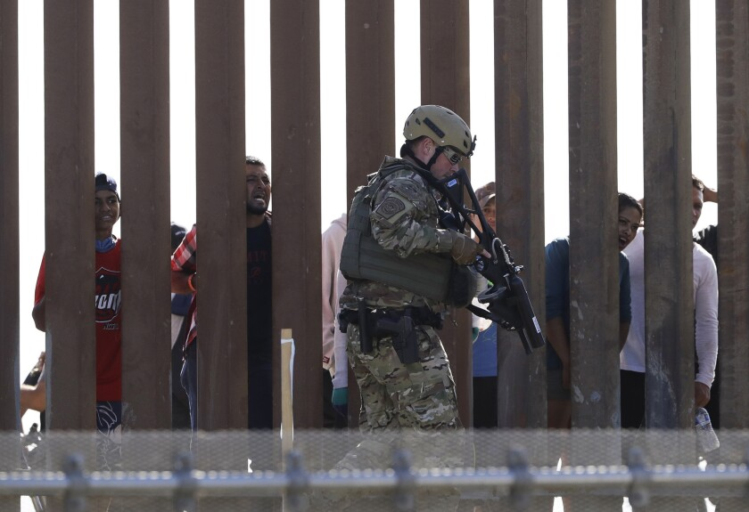 Border Patrol officers walk along a wall at the border between Mexico and the U.S., as seen from San Diego on Sunday.