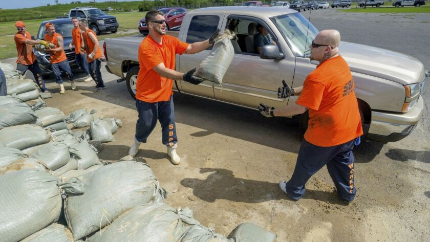 St. Bernard Parish jail inmates help residents load sandbags in Chalmette, La., on Thursday, ahead of the arrival of Tropical Storm Barry.