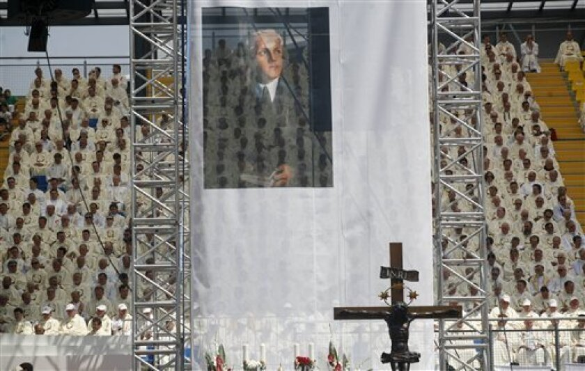 A photo of  Lojze Grozde is displayed in front of Roman Catholic priests attending the mass in Celje, Slovenia, Sunday, June 13, 2010. Grozde, who died in 1943 at the age of 20, is the first beatified martyr in the predominantly Roman Catholic country,  ruled by the communists until its 1991 indepe
