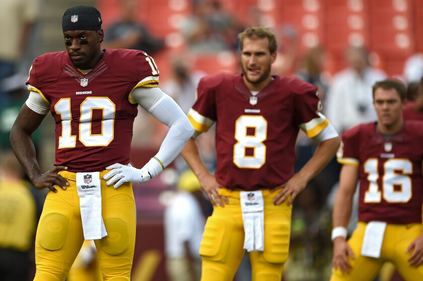Washington quarterbacks Robert Griffin III, left, and Kirk Cousins watch during a preseason game against New England on Aug. 7.
