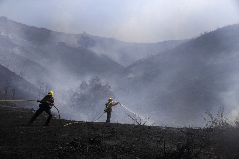 Firefighters put out hotspots from the Elsmere fire, fueled by hot and dry temperatures Monday, Aug. 3, 2020, in Santa Clarita, Calif. (AP Photo/Marcio Jose Sanchez)
