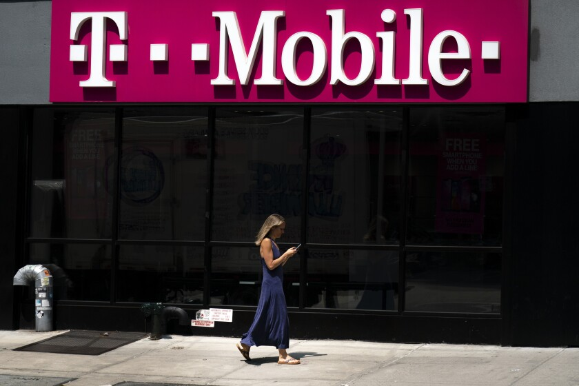 A woman looks at her phone as she walks by a T-Mobile store