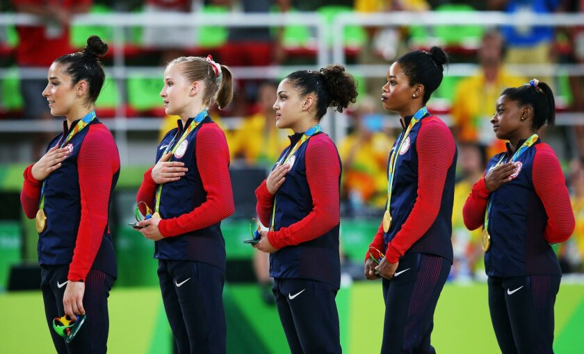 RIO DE JANEIRO, BRAZIL - AUGUST 09:  (R to L) Gold Medalists Simone Biles, Gabrielle Douglas, Lauren Hernandez, Madison Kocian and Alexandra Raisman of the United States stand on the podium for the national anthem at the medal ceremony for the Artistic Gymnastics Women's Team Final on Day 4 of the