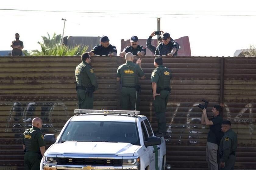 Fotografía del 26 de octubre de 2017, donde aparece el subcomisionado interino de la Oficina de Aduanas y Protección Fronteriza (CBP) de los Estados Unidos, Ron Vitiello (c-de espaldas), conversando con miembros de la Policía Federal (PF) de México (arriba), durante una visita a la frontera que separa los dos países y en donde se presentaron los prototipos de muros a los periodistas, en San Diego (EE.UU.). EFE/Archivo