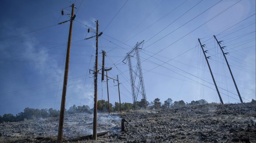 In this Wednesday, July 4, 2018 photo, a powerline dangles and burns in a wildfire in Basalt, Colo.