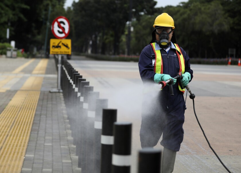 A worker sprays disinfectant at the pedestrian walkway at Senayan Sports Complex in Jakarta, Indonesia.