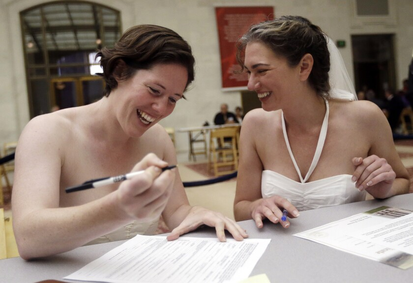 Cynthia Wides, right, and Elizabeth Carey file for a marriage certificate at City Hall in San Francisco on June 29, 2013. A new law will change state code to use gender-neutral terms for marriage.