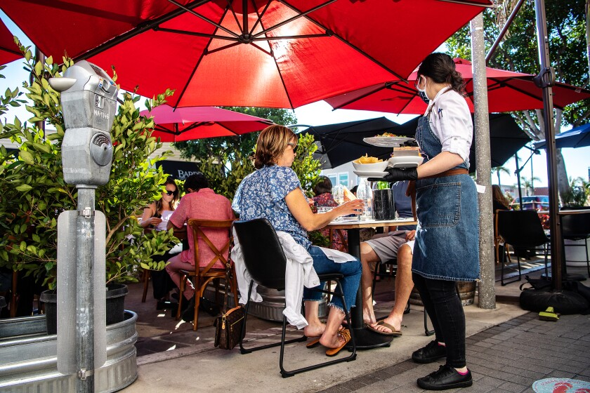 Customers dine outside on a patio with umbrellas as a server walks by wearing a mask.