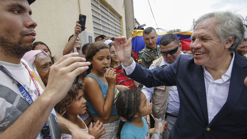 The Secretary-General of the Organization of American States, Uruguayan Luis Almagro, right, greets Venezuelans during his visit to the Divina Providencia migrant shelter in Cucuta, Colombia, on the border with Venezuela, on Sept. 14, 2018.