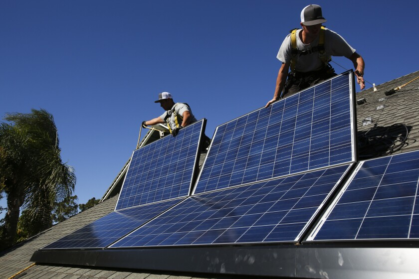 Jobs in the U.S. solar industry grew 21.8% in 2014 as the price of panels fell and demand grew. Above, Rogelio Mora, left, and Tyler Smith, workers from vivint.solar, install solar panels on the roof of a home in Camarillo.
