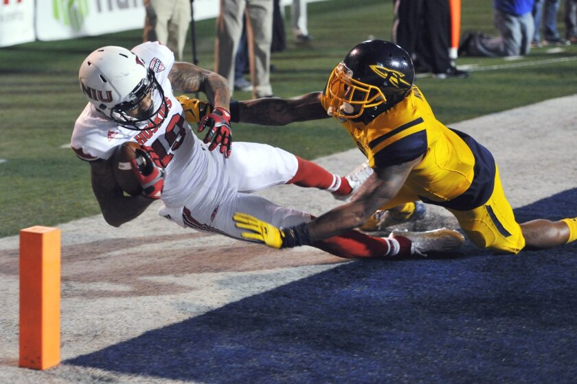 Northern Illinois wide receiver Kenny Golladay, left, catches a touchdown pass while defended by Toledo cornerback Cheatham Norrils during the fourth quarter of an NCAA college football game Tuesday, Nov. 3, 2015, in Toledo, Ohio. (AP Photo/David Richard)