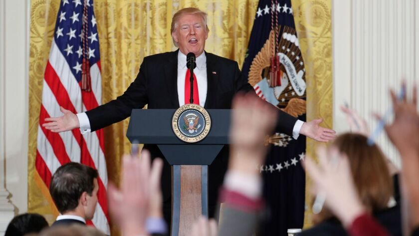 Reporters raise their hands as President Donald Trump fields questions during a news conference in the East Room of the White House in Washington on Feb. 16.
