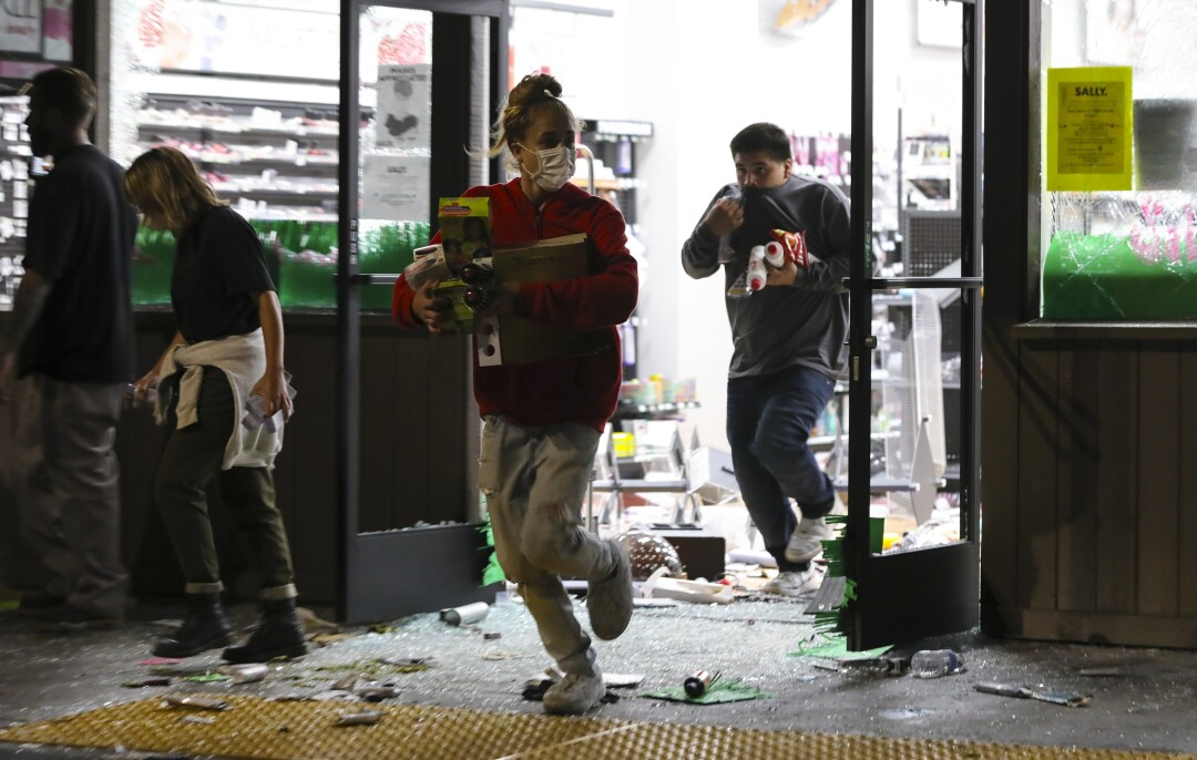 By nightfall on Saturday, looters had smashed windows and taken items from a number of retail stores at the La Mesa Springs shopping center.