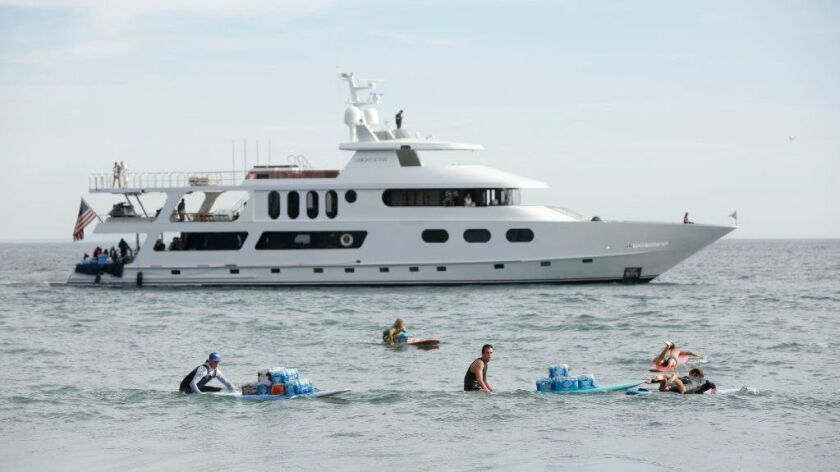 Residents and volunteers bring in supplies for those in Malibu off of a billionaire's yacht.