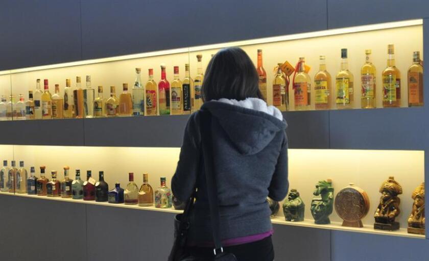 Fotografía de una mujer observando una vitrina con botellas de tequila en Ciudad de México. EFE/Archivo