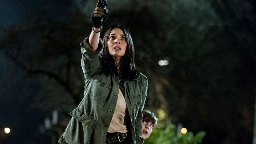 "Olivia Munn shielding Jacob Tremblay in ""The Predator."""