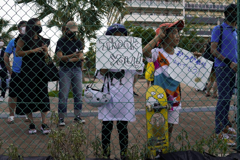 Two girls hold signs while waiting to get a glimpse of Yuto Horigome, the first Olympic gold medalist in skateboarding, outside the Ariake Urban Sports Park during the 2020 Summer Olympics, Sunday, July 25, 2021, in Tokyo. (AP Photo/Jae C. Hong)