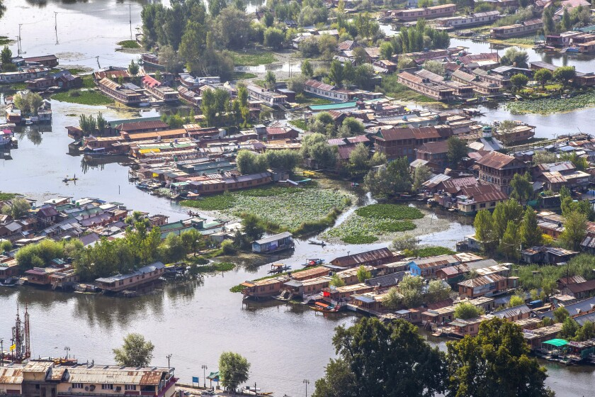 A view of the Dal Lake in Srinagar, Indian controlled Kashmir, Saturday, Aug. 28, 2021. Weeds, silt and untreated sewage are increasingly choking the sprawling scenic lake, which dominates the city and draws tens of thousands of tourists each year. (AP Photo/Mukhtar Khan)