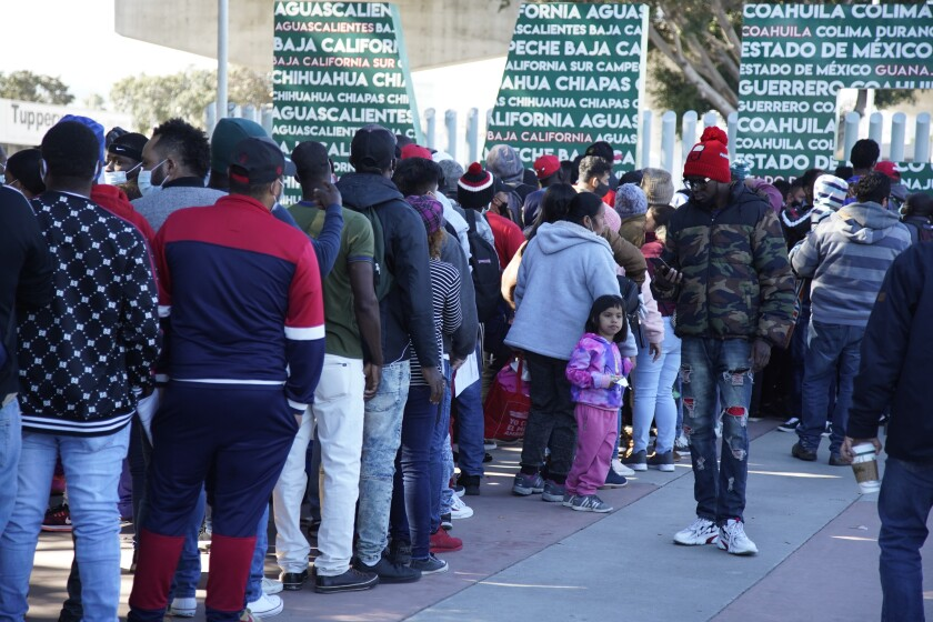 People stand in line at a border crossing